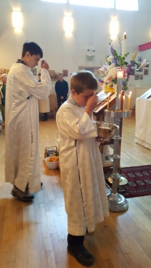The acolytes venerate the icon of the feast.