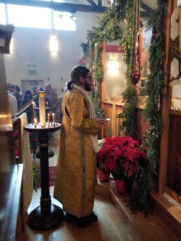 Philip stands before the icon of Christ holding the bolw and ewer of water with which he will wash the bishop's hands. Phot courtesy of Joanna Slinkert.